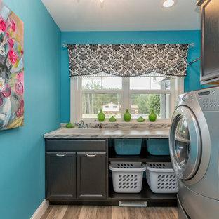 他の地域のトランジショナルスタイルのおしゃれな洗濯室 (ドロップインシンク、落し込みパネル扉のキャビネット、黒いキャビネット、青い壁、淡色無垢フローリング、左右配置の洗濯機・乾燥機、ベージュの床、グレーのキッチンカウンター) の写真