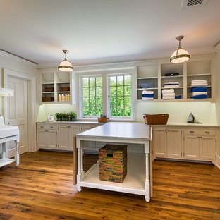 Large elegant l-shaped light wood floor and brown floor dedicated laundry room photo in Philadelphia with a farmhouse sink, white cabinets, shaker cabinets, wood countertops, white walls, a side-by-side washer/dryer and beige countertops