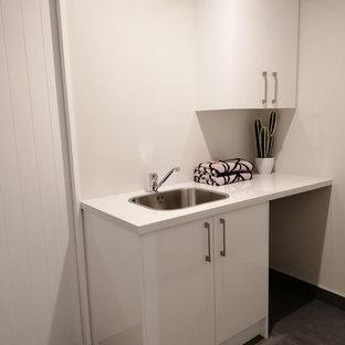 Exempel på en liten modern vita linjär vitt tvättstuga enbart för tvätt och med garderob, med en nedsänkt diskho, släta luckor, vita skåp, laminatbänkskiva, vita väggar, linoleumgolv och grått golv