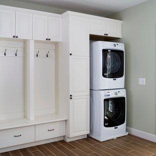 Foto di una lavanderia multiuso chic di medie dimensioni con ante con bugna sagomata, ante bianche, pavimento in vinile, lavatrice e asciugatrice a colonna, pavimento marrone e pareti grigie