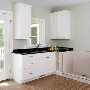 Idéer för en mellanstor klassisk l-formad tvättstuga enbart för tvätt, med luckor med upphöjd panel, vita skåp, vinylgolv, brunt golv, granitbänkskiva, grå väggar och en undermonterad diskho