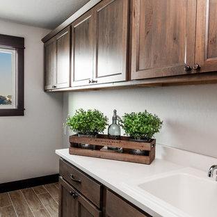 Bild på en mellanstor lantlig vita linjär vitt tvättstuga enbart för tvätt, med en nedsänkt diskho, skåp i shakerstil, skåp i slitet trä, bänkskiva i kvarts, vita väggar, klinkergolv i porslin, en tvättmaskin och torktumlare bredvid varandra och flerfärgat golv