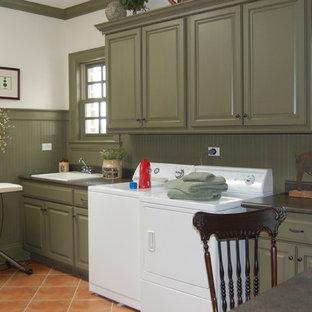シカゴのトラディショナルスタイルのおしゃれなランドリールーム (ドロップインシンク、レイズドパネル扉のキャビネット、緑のキャビネット、左右配置の洗濯機・乾燥機、テラコッタタイルの床、赤い床、白い壁) の写真
