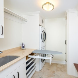Inspiration for a small transitional single-wall dedicated laundry room in Toronto with an undermount sink, flat-panel cabinets, white cabinets, quartz benchtops, white walls, marble floors and a stacked washer and dryer.