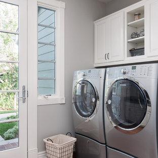Klassisk inredning av en stor tvättstuga, med en rustik diskho, luckor med infälld panel, vita skåp, bänkskiva i kvartsit, grått stänkskydd, stänkskydd i stenkakel och mellanmörkt trägolv