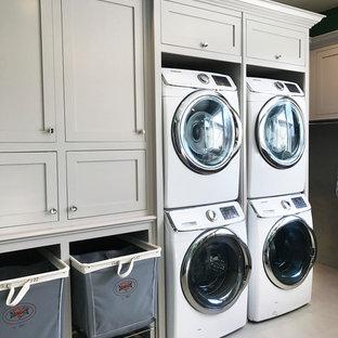 Esempio di un'ampia lavanderia multiuso tradizionale con pareti verdi e lavatrice e asciugatrice a colonna