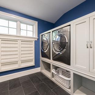 Exempel på en mellanstor klassisk parallell tvättstuga enbart för tvätt, med en undermonterad diskho, vita skåp, blå väggar, en tvättmaskin och torktumlare bredvid varandra, skiffergolv och luckor med infälld panel