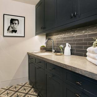 Immagine di una sala lavanderia tradizionale con lavello sottopiano, ante in stile shaker, ante nere, pareti bianche, lavatrice e asciugatrice a colonna, pavimento multicolore e top grigio