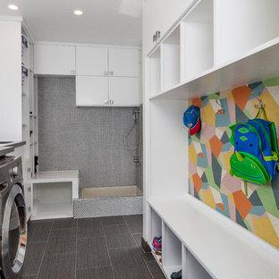 Bild på ett mellanstort 60 tals u-format grovkök, med en enkel diskho, släta luckor, vita skåp, bänkskiva i kvarts, vita väggar, klinkergolv i keramik och en tvättmaskin och torktumlare bredvid varandra