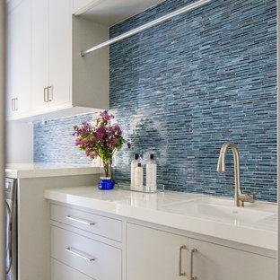 Idéer för stora medelhavsstil parallella vitt tvättstugor enbart för tvätt, med en undermonterad diskho, släta luckor, grå skåp, blå väggar, en tvättmaskin och torktumlare bredvid varandra och blått golv