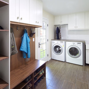 Example of a trendy brown floor laundry room design in Denver with a farmhouse sink and white cabinets