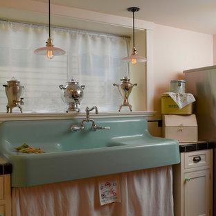 Foto på en mellanstor vintage parallell tvättstuga enbart för tvätt, med en rustik diskho, luckor med infälld panel, vita skåp, kaklad bänkskiva, rosa väggar, ljust trägolv och en tvättpelare