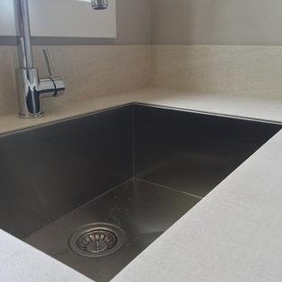 Inredning av en modern mellanstor tvättstuga enbart för tvätt, med en undermonterad diskho, skåp i shakerstil, vita skåp, laminatbänkskiva, grå väggar och en tvättmaskin och torktumlare bredvid varandra