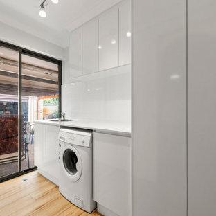 Inspiration för mellanstora moderna linjära vitt tvättstugor enbart för tvätt, med en nedsänkt diskho, skåp i shakerstil, vita skåp, vita väggar och gult golv