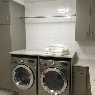Inredning av en klassisk stor l-formad tvättstuga enbart för tvätt, med en nedsänkt diskho, släta luckor, grå skåp, bänkskiva i koppar, grå väggar, klinkergolv i porslin, en tvättmaskin och torktumlare bredvid varandra och vitt golv