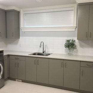 Large classic l-shaped separated utility room in Other with a built-in sink, flat-panel cabinets, grey cabinets, composite countertops, grey walls, porcelain flooring, a side by side washer and dryer and white floors.