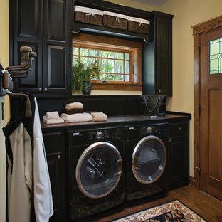 Esempio di una sala lavanderia rustica di medie dimensioni con ante nere, pareti beige, parquet scuro, ante con bugna sagomata e lavatrice e asciugatrice affiancate