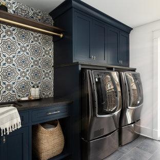 Inspiration för mellanstora klassiska svart grovkök, med en undermonterad diskho, släta luckor, blå skåp, bänkskiva i kvarts, vita väggar, klinkergolv i porslin, en tvättmaskin och torktumlare bredvid varandra och grått golv
