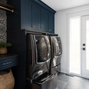 Lantlig inredning av ett mellanstort svart svart grovkök, med en undermonterad diskho, släta luckor, blå skåp, bänkskiva i kvarts, vita väggar, klinkergolv i porslin, en tvättmaskin och torktumlare bredvid varandra och grått golv