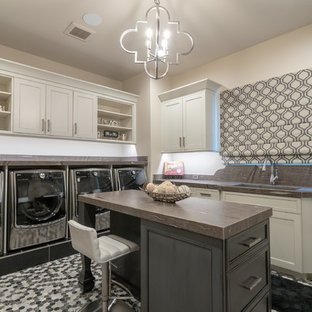 Southwest multicolored floor dedicated laundry room photo in Phoenix with an undermount sink, recessed-panel cabinets, beige cabinets, beige walls, a side-by-side washer/dryer and brown countertops