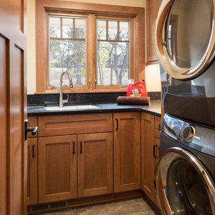 Esempio di una sala lavanderia di medie dimensioni con lavello sottopiano, ante con riquadro incassato, ante in legno scuro, top in quarzo composito, pareti beige, lavatrice e asciugatrice a colonna e pavimento verde