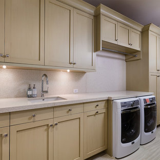 Large elegant single-wall ceramic floor and beige floor dedicated laundry room photo in Other with an undermount sink, recessed-panel cabinets, light wood cabinets, recycled glass countertops, beige walls, a side-by-side washer/dryer and beige countertops