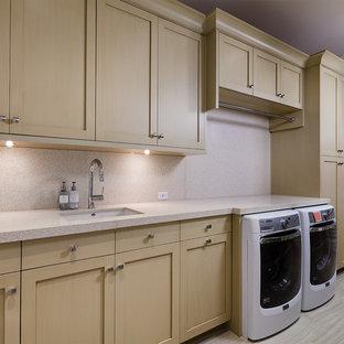 Bild på en stor vintage beige linjär beige tvättstuga enbart för tvätt, med en undermonterad diskho, luckor med infälld panel, skåp i ljust trä, bänkskiva i återvunnet glas, beige väggar, klinkergolv i keramik, en tvättmaskin och torktumlare bredvid varandra och beiget golv