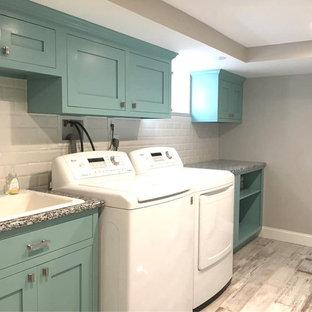 Inspiration för mellanstora moderna linjära flerfärgat tvättstugor enbart för tvätt, med en rustik diskho, skåp i shakerstil, turkosa skåp, granitbänkskiva, grå väggar, mellanmörkt trägolv och flerfärgat golv