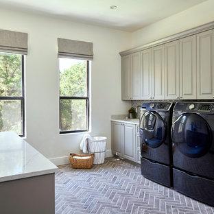 Klassisk inredning av en beige parallell beige tvättstuga, med en undermonterad diskho, luckor med upphöjd panel, grå skåp, vita väggar, tegelgolv, en tvättmaskin och torktumlare bredvid varandra och brunt golv