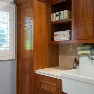 Idéer för att renovera en mellanstor funkis parallell tvättstuga enbart för tvätt, med en rustik diskho, skåp i shakerstil, skåp i mellenmörkt trä, bänkskiva i kalksten, blå väggar och en tvättmaskin och torktumlare bredvid varandra
