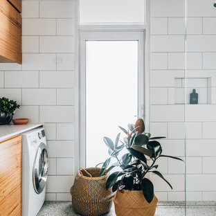 Inspiration for a contemporary single-wall laundry room in Melbourne with flat-panel cabinets, medium wood cabinets, white walls, white floor and white benchtop.