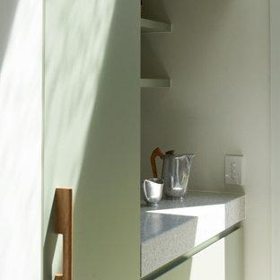 Cette photo montre une buanderie parallèle tendance multi-usage avec un évier 1 bac, des portes de placards vertess, un plan de travail en terrazzo, un mur blanc, un sol en carrelage de céramique, des machines superposées, un sol gris et un plan de travail gris.
