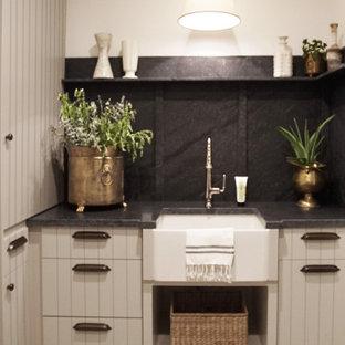 Exempel på en mellanstor svarta u-formad svart tvättstuga enbart för tvätt, med en rustik diskho, släta luckor, grå skåp, granitbänkskiva, svart stänkskydd, vita väggar och en tvättmaskin och torktumlare bredvid varandra