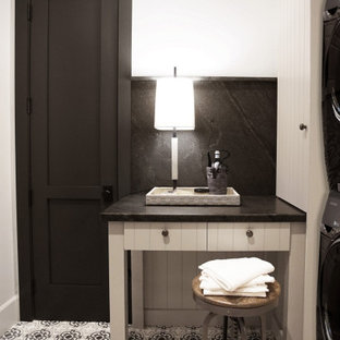 Mid-sized u-shaped dedicated laundry room in Phoenix with a farmhouse sink, flat-panel cabinets, grey cabinets, granite benchtops, black splashback, white walls, a side-by-side washer and dryer and black benchtop.