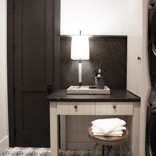 Ispirazione per una sala lavanderia di medie dimensioni con lavello stile country, ante lisce, ante grigie, top in granito, paraspruzzi nero, paraspruzzi in granito, pareti bianche, lavatrice e asciugatrice affiancate e top nero