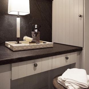 Idéer för en mellanstor svarta u-formad tvättstuga enbart för tvätt, med en rustik diskho, släta luckor, grå skåp, granitbänkskiva, svart stänkskydd, vita väggar och en tvättmaskin och torktumlare bredvid varandra