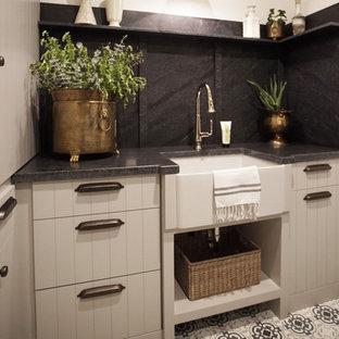 Idéer för att renovera en mellanstor svarta u-formad svart tvättstuga enbart för tvätt, med en rustik diskho, släta luckor, grå skåp, granitbänkskiva, svart stänkskydd, vita väggar och en tvättmaskin och torktumlare bredvid varandra