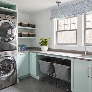 Immagine di una sala lavanderia costiera con lavello sottopiano, ante in stile shaker, ante verdi, pareti bianche, pavimento grigio e top grigio
