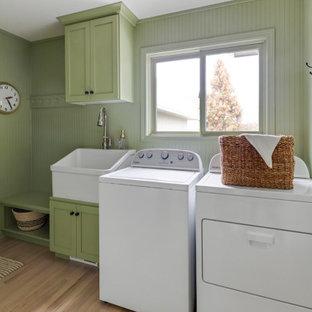 Idee per un'ampia sala lavanderia country con lavello stile country, ante in stile shaker, ante verdi, top in quarzite, pareti verdi, parquet chiaro, lavatrice e asciugatrice affiancate e top bianco