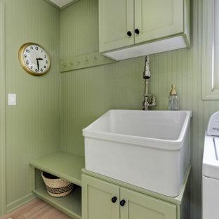 Immagine di un'ampia sala lavanderia country con lavello stile country, ante in stile shaker, ante verdi, top in quarzite, pareti verdi, parquet chiaro, lavatrice e asciugatrice affiancate e top bianco