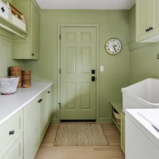 Ispirazione per un'ampia sala lavanderia country con lavello stile country, ante in stile shaker, ante verdi, top in quarzite, pareti verdi, parquet chiaro, lavatrice e asciugatrice affiancate e top bianco