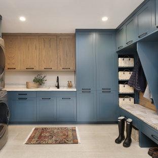 Immagine di una lavanderia multiuso rustica con lavello sottopiano, ante in stile shaker, ante blu, lavatrice e asciugatrice a colonna, pavimento grigio e top bianco