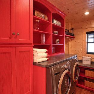 Inspiration pour une buanderie linéaire chalet dédiée et de taille moyenne avec un placard à porte plane, des portes de placard rouges, un plan de travail en stratifié, un mur marron, un sol en bois brun et des machines côte à côte.