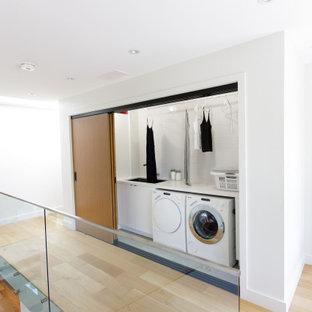 Idées déco pour une buanderie moderne avec un placard, un évier intégré, un placard sans porte, des portes de placard blanches, un sol en bois brun, des machines côte à côte, un sol marron et un plan de travail blanc.