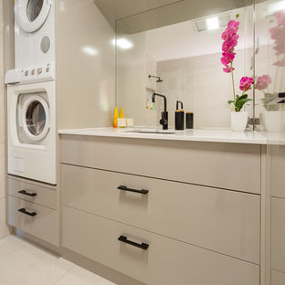 Photo of a mid-sized contemporary single-wall utility room in Brisbane with quartz benchtops, porcelain floors, a stacked washer and dryer, beige floor, an undermount sink, flat-panel cabinets, beige cabinets, beige walls and white benchtop.