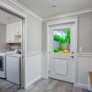 Idee per una lavanderia multiuso tradizionale di medie dimensioni con ante in stile shaker, ante bianche, pareti grigie, pavimento in gres porcellanato, lavatrice e asciugatrice affiancate e pavimento grigio