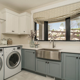Laundry room - farmhouse gray floor laundry room idea in Salt Lake City with a farmhouse sink, shaker cabinets, blue cabinets, beige walls and white countertops