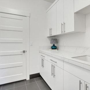 Exempel på en mellanstor modern vita parallell vitt tvättstuga enbart för tvätt, med en nedsänkt diskho, släta luckor, vita skåp, kaklad bänkskiva, vita väggar, betonggolv, en tvättmaskin och torktumlare bredvid varandra och grått golv