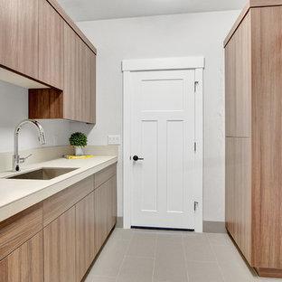 Amerikansk inredning av en liten parallell tvättstuga enbart för tvätt, med en nedsänkt diskho, släta luckor, kaklad bänkskiva, grå väggar, klinkergolv i keramik, en tvättmaskin och torktumlare bredvid varandra, grått golv och skåp i mellenmörkt trä