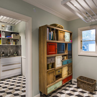 Large victorian dedicated laundry room in Wellington with an utility sink, granite benchtops, blue walls, porcelain floors and a side-by-side washer and dryer.